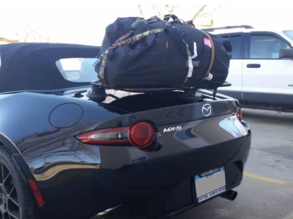 revo-rack mazda nd luggage rack in black fitted to a black nd miata with a large black luggage bag on it