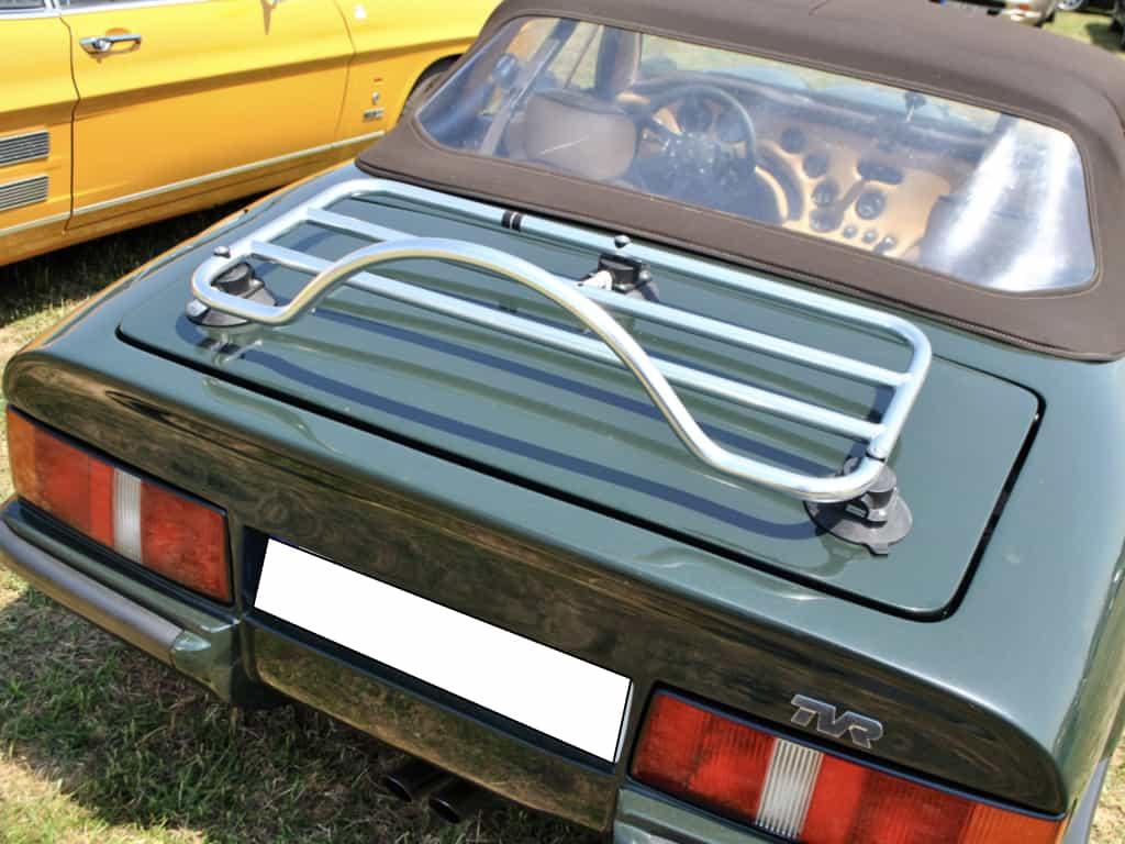 Convertible TVR verte avec un porte-bagages en acier inoxydable installée dans un champ par une journée ensoleillée