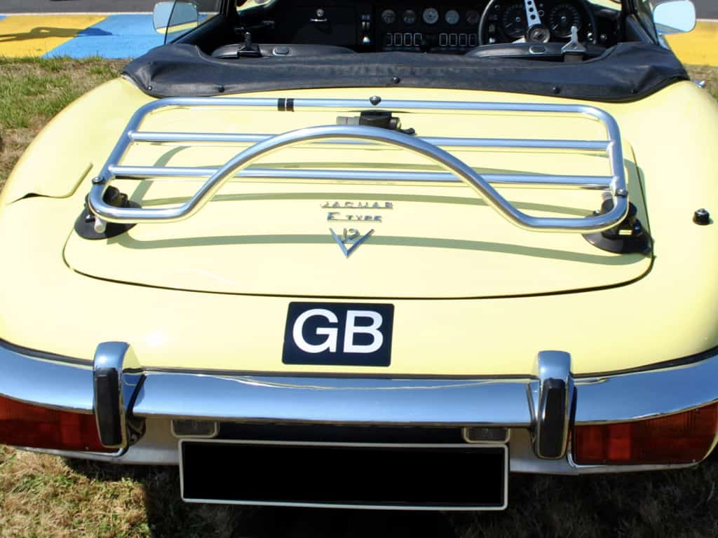 stainless steel luggage rack fitted to a yellow jaguar e type convertible