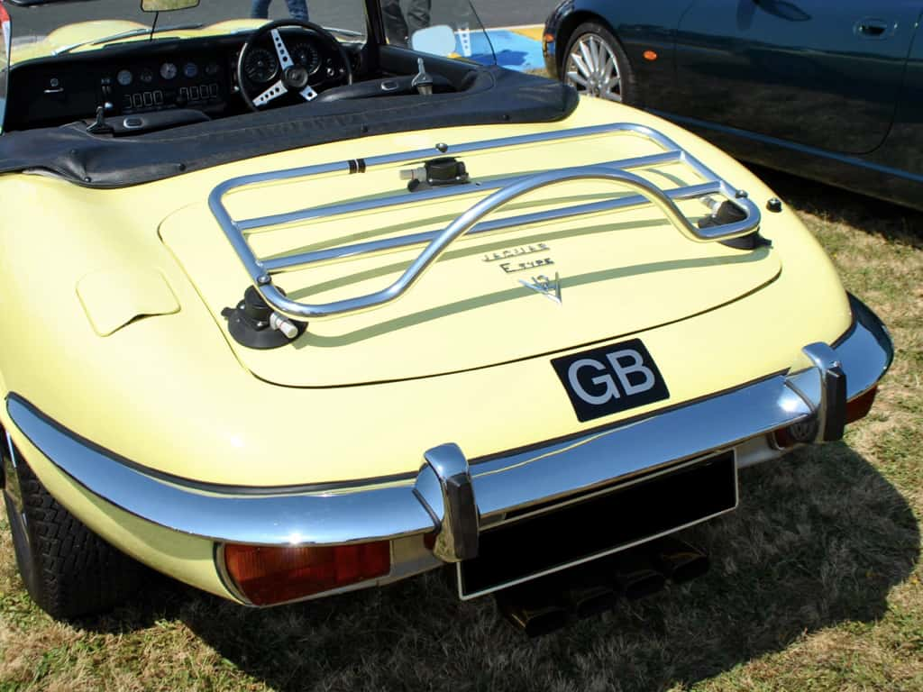 dusty yellow jaguar e type convertible with a stainless steel trunk rack fitted