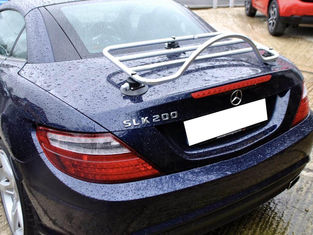bleu foncé mercedes benx slk avec un porte-bagages en acier inoxydable monté sous la pluie