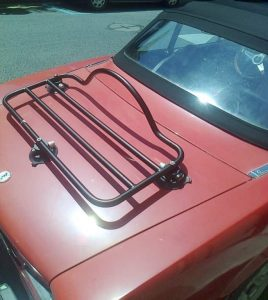revo-rack black luggage rack fitted to a red classic fiat 124 spider in the sunshine.