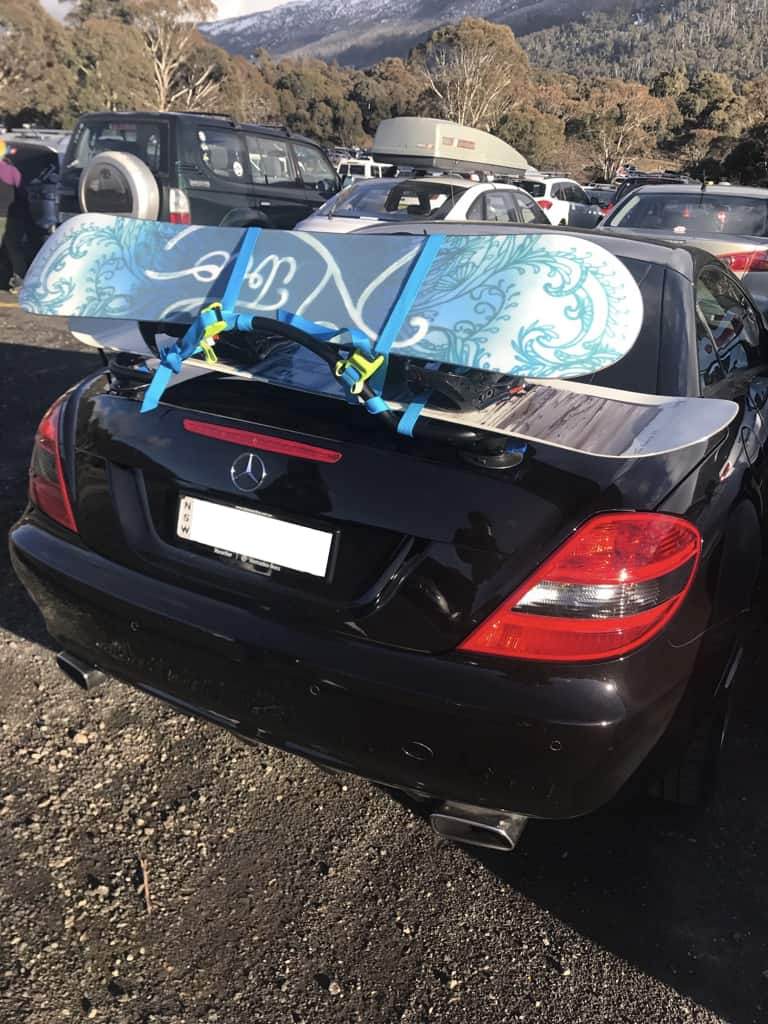 Convertible ski rack fitted to a mercedes slk in black with two snowboards on it