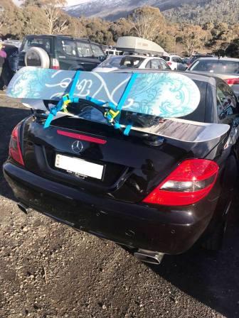Mercedes slk noir avec un porte-bagages muni de deux snowboards attachés au porte-bagages