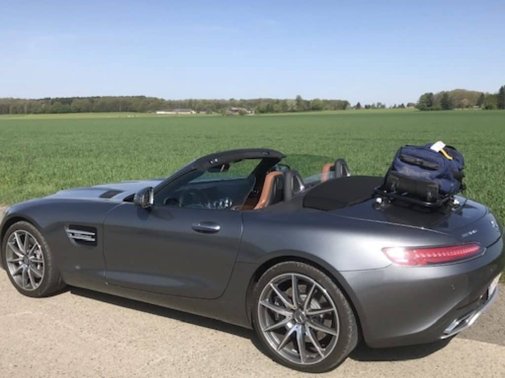 side view of an AMG GT cabrio with a luggage rack fitted and suitcase on it next to a field on a sunny day
