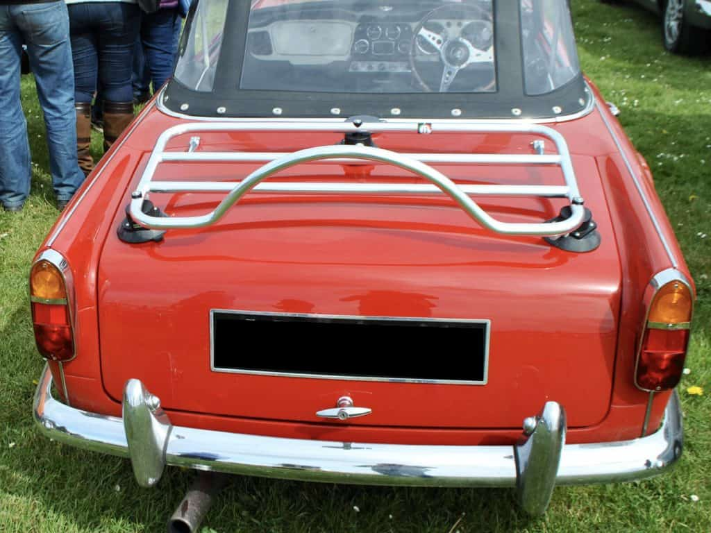 red triumph tr5 in a field with a revo rack luggage rack fitted to it