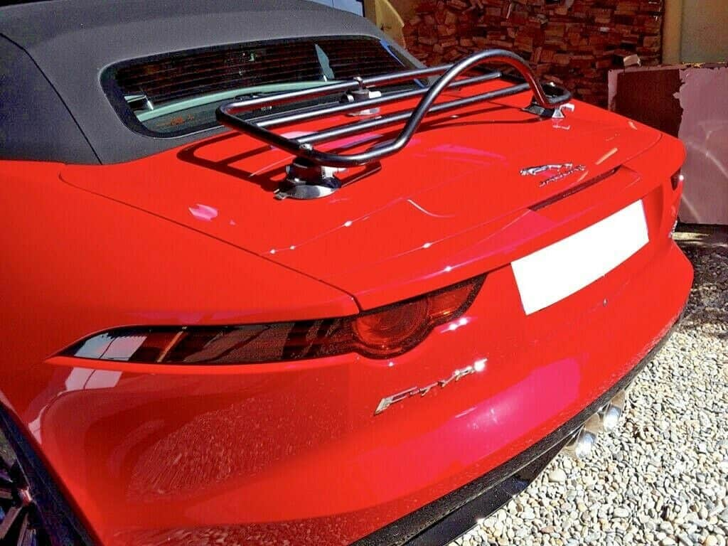 red jaguar f type convertible with a black luggage rack fitted