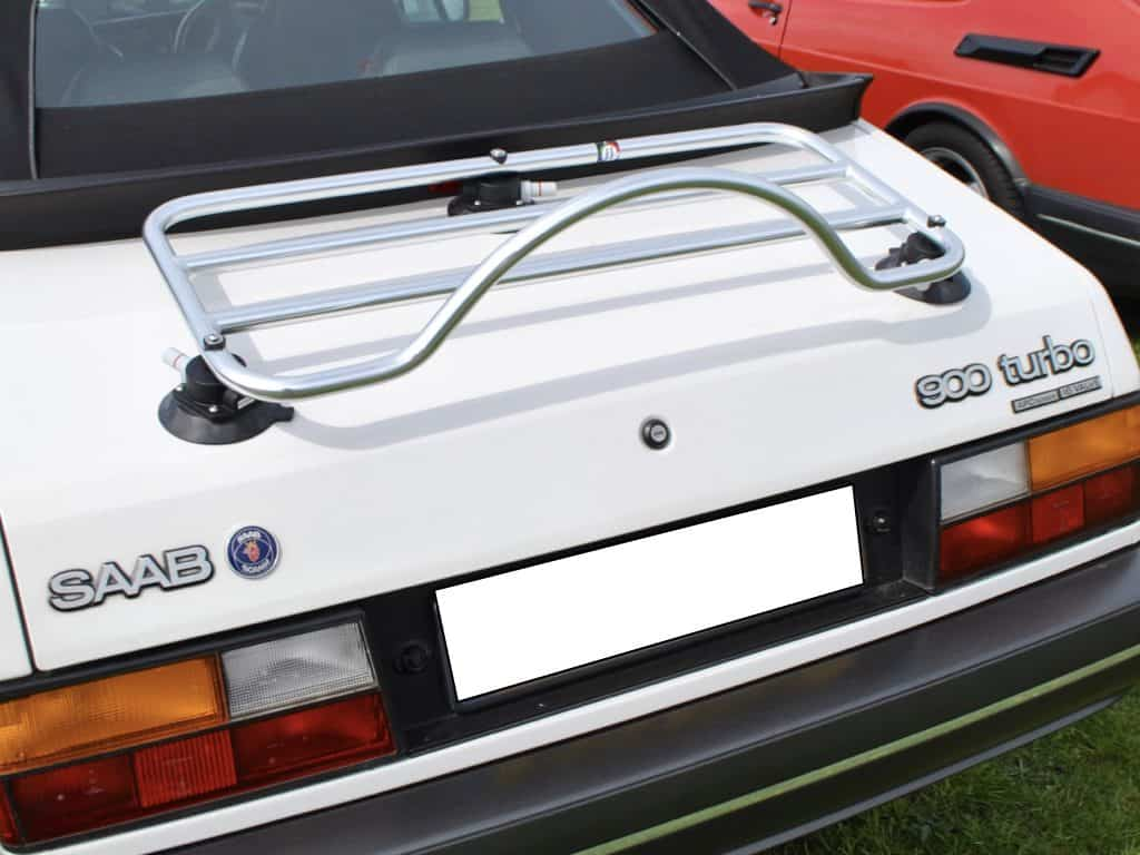 classic white saab 900 convertible with a luggage rack fitted